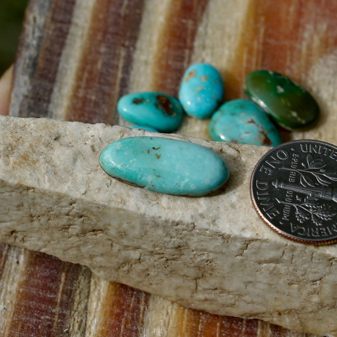 A natural light blue turquoise cabochon oval (Stone Mountain Turquoise)  $14 for 5.2 carat untreated Nevada turquoise. This cabochon has a thin strip of natural hostrock backing.